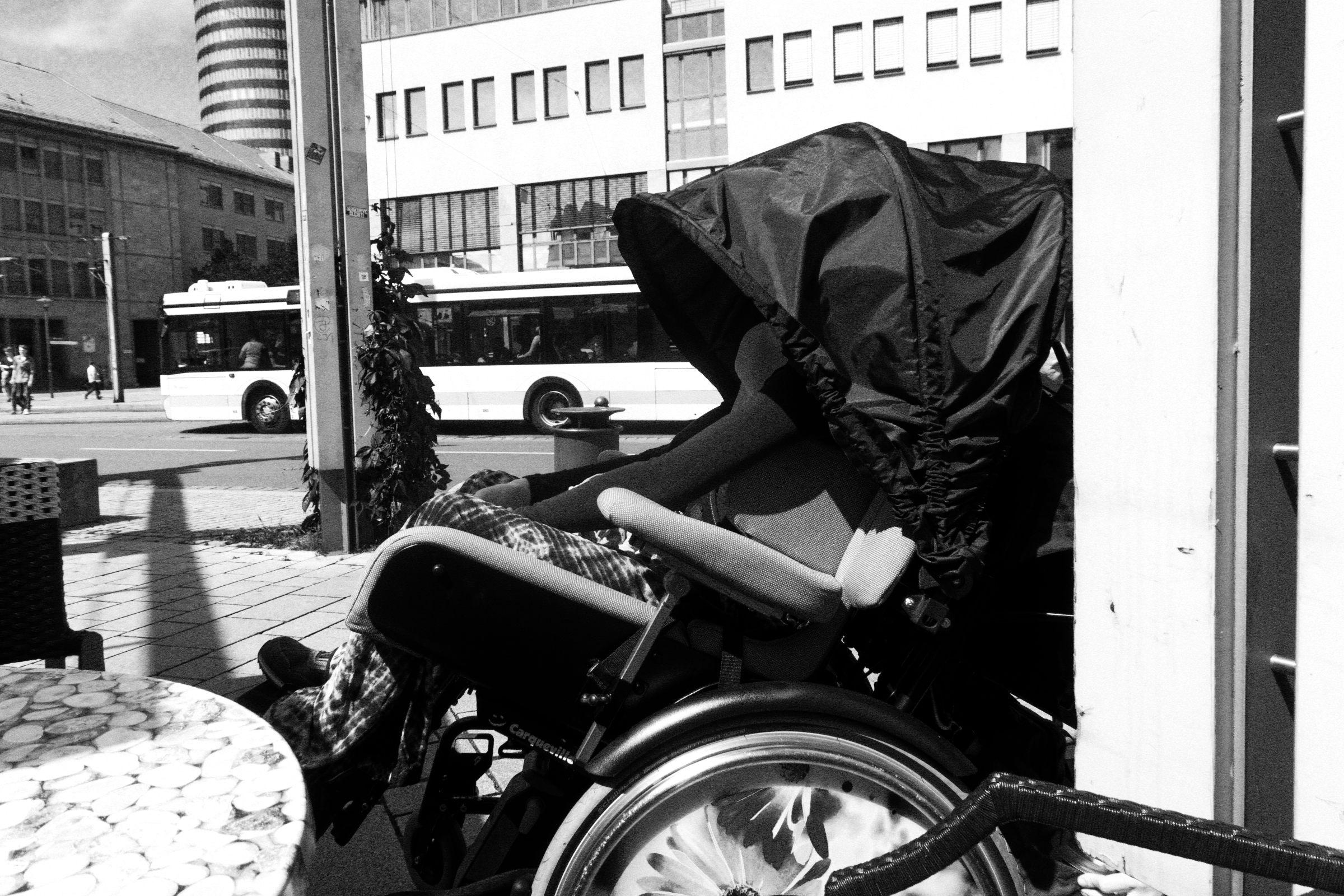 Rollstuhl mit Verdeck in der Stadt in Schwarz-Weiß